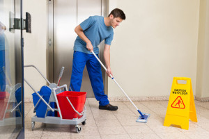 45703699 - happy male janitor with cleaning equipments mopping floor
